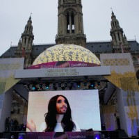 Conchita Wurst greets vitors from teh big screen in front of Vienna's town hall